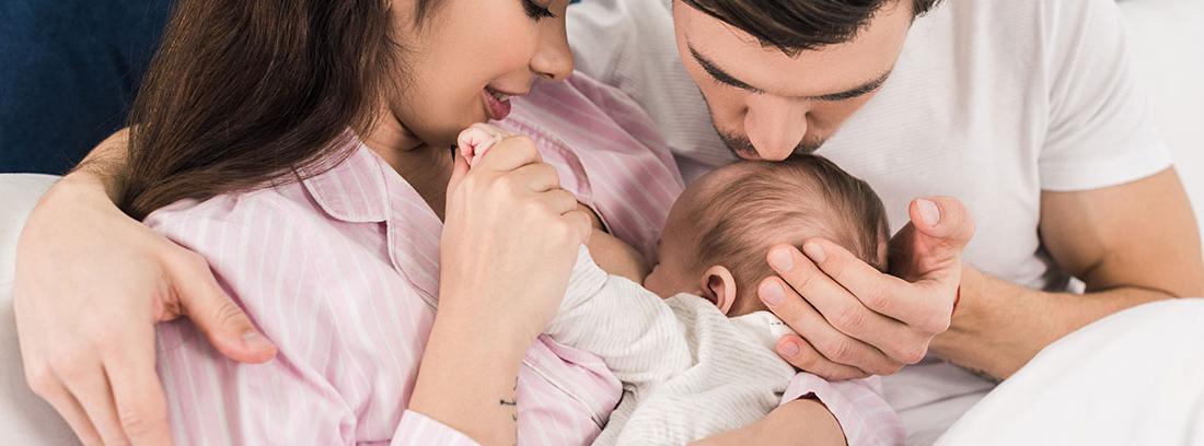 Pareja mirando a un bebé mientras toma el pecho