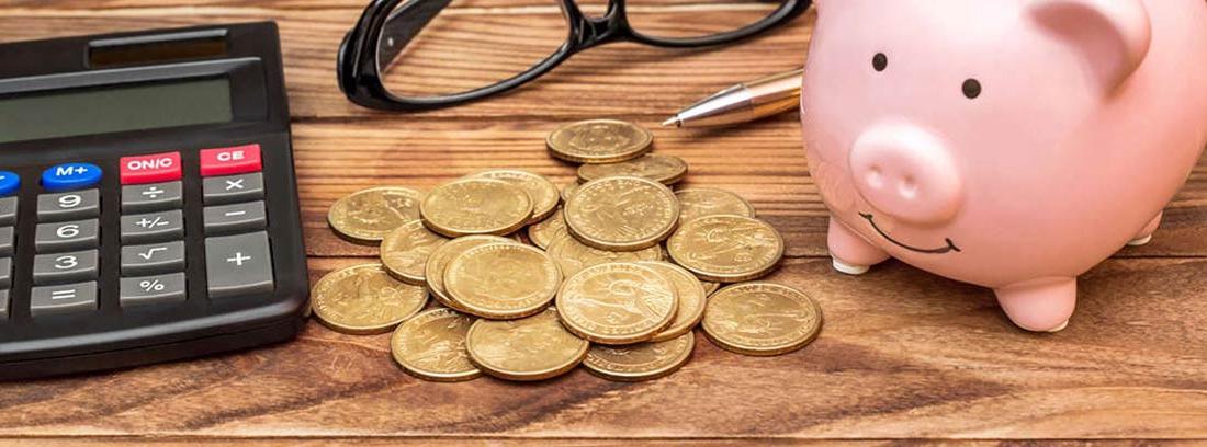 Hucha de cerdo junto a unas gafas, unas monedas y una calculadora