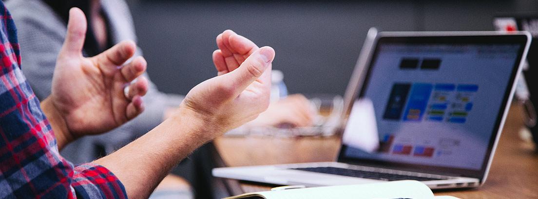 Manos abiertas delante de una mesa con ordenador portátil y teléfono móvil