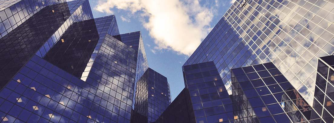 Edificios altos acristalados contra cielo azul con nubes