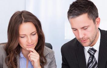 Hombre y mujer con traje rellenando el modelo 202 de impuesto de sociedades