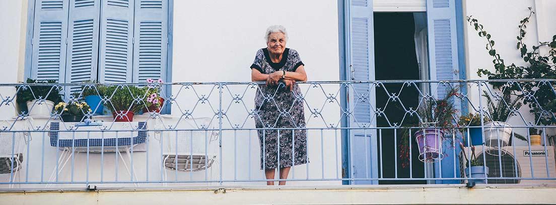 Mujer con pelo blanco apoya sus manos sobre la barandilla de la terraza de una casa