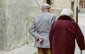 Mujer con bastón y hombre caminan por la calle de una ciudad