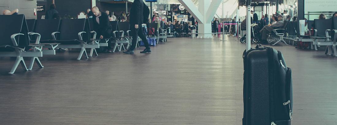 Maleta de ruedas negra en zona de espera de embarque de aeropuerto