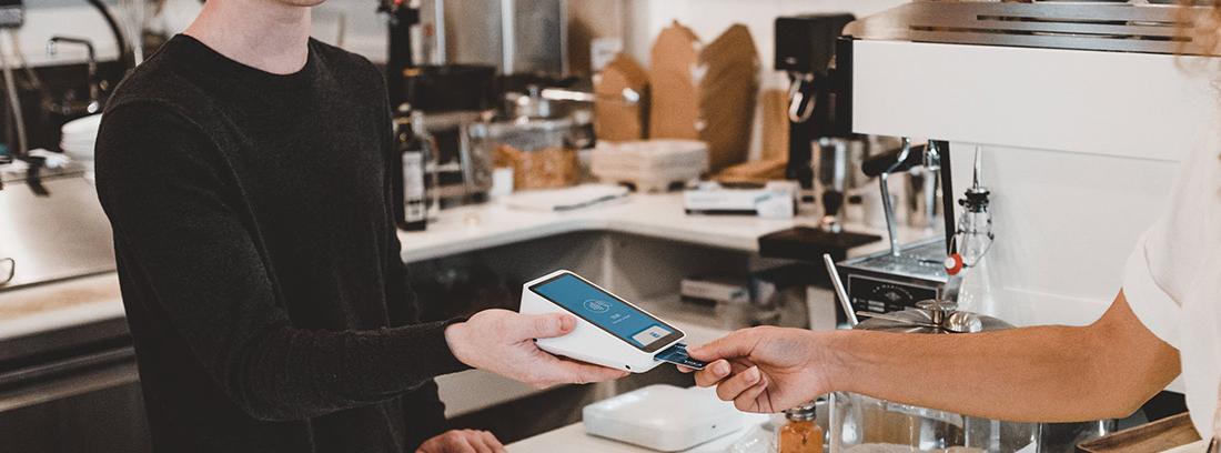 Persona detrás de barra sujeta lector de tarjetas de crédito mientras otro pone su tarjeta