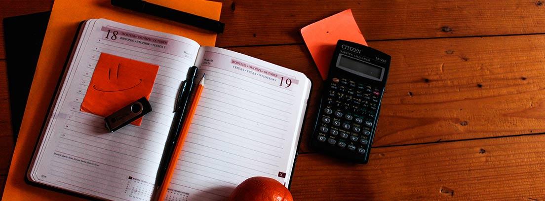 Agenda de papel abierta con lápices y junto a calculadora