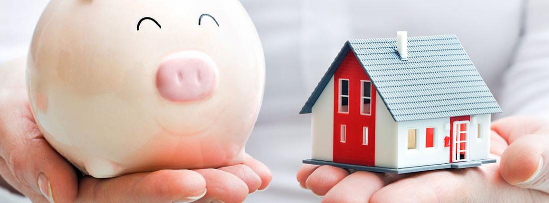 Hombre sujetando en una mano una hucha de cerdo y en la otra, la maqueta de una casa