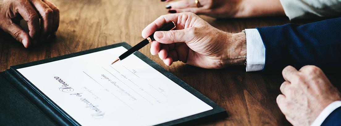 Varias manos alrededor de unos documentos de divorcio