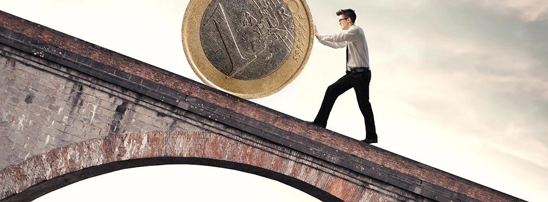 Hombre empujando una moneda de euro por una pendiente