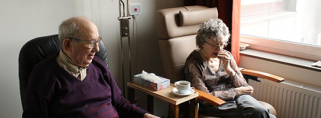 Mujer y hombre mayor sentados junto a ventana