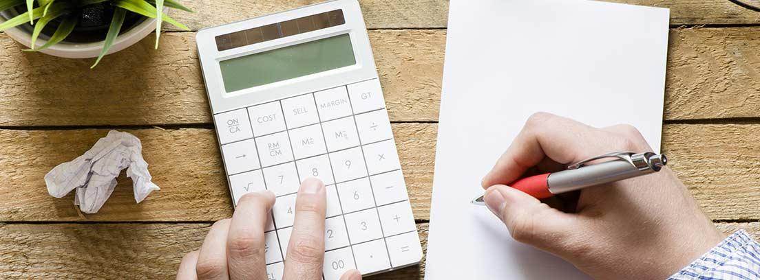 Manos con una calculadora y una libreta