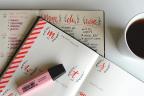 Agenda abierta sobre otros junto a una taza de café y un marcador rosa