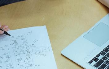 Mano con bolígrafo sobre papel y la otra sobre teclado ordenador portátil