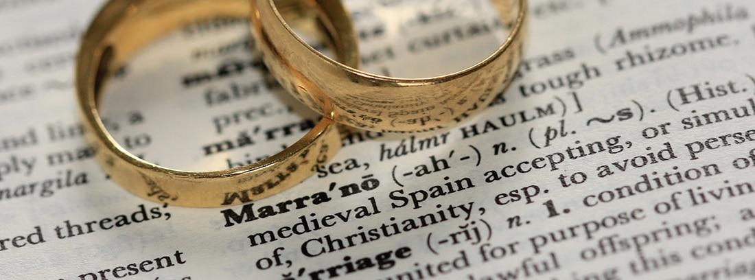 Dos alianzas de oro amarillo sobre un papel con texto mecanografiado en negro