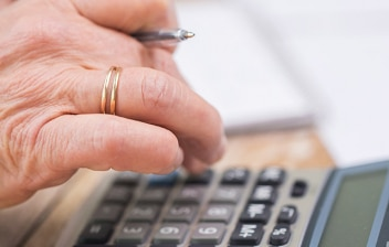 Mano de una persona de avanzada edad usando una calculadora