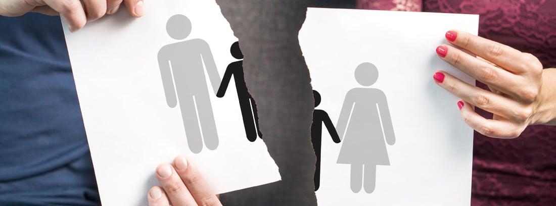 Hombre y mujer sujetando un papel roto con un dibujo de una familia partida por la mitrad