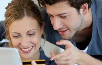 Pareja sonriente con una yablet y una tarjeta de crédito en la mano