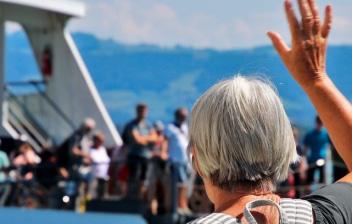 Persona mayor de espaldas con mochila y levantando una mano acercándose a un barco