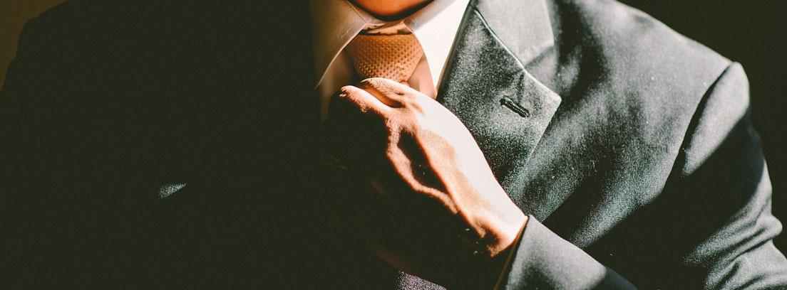 Hombre ajustándose la corbata del traje
