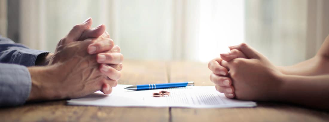 Manos de hombre sobre una mesa con manos de mujer en frente y unos papeles y alianzas en el medio