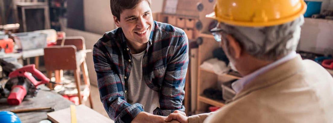 Dos hombres, uno con casco de obra amarillo, se estrechan las manos