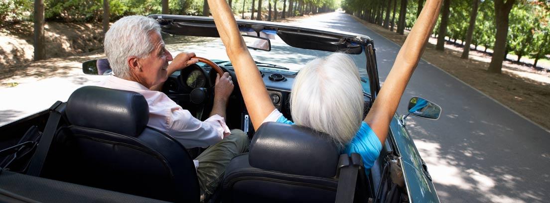Dos personas mayores felices en un descapotable
