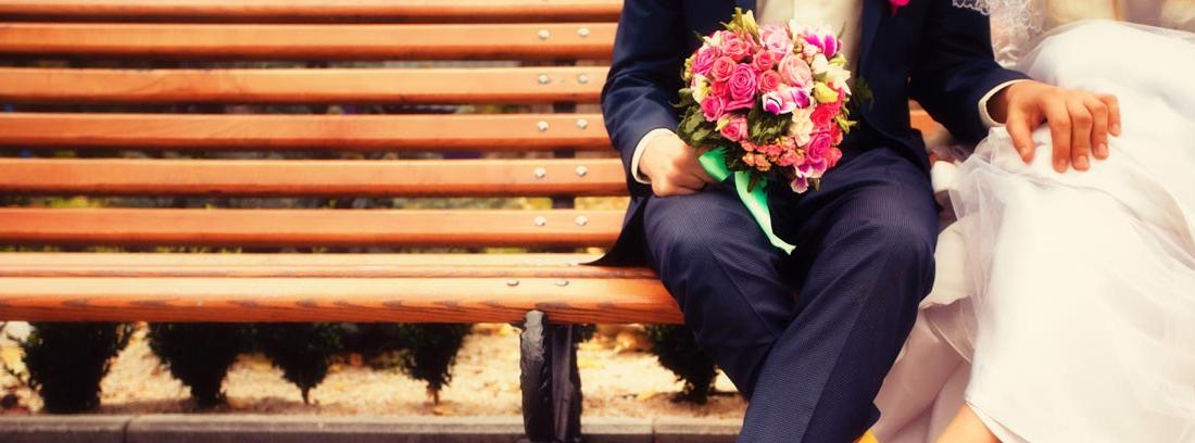 Pies de pareja de novios modernos sentados en un banco