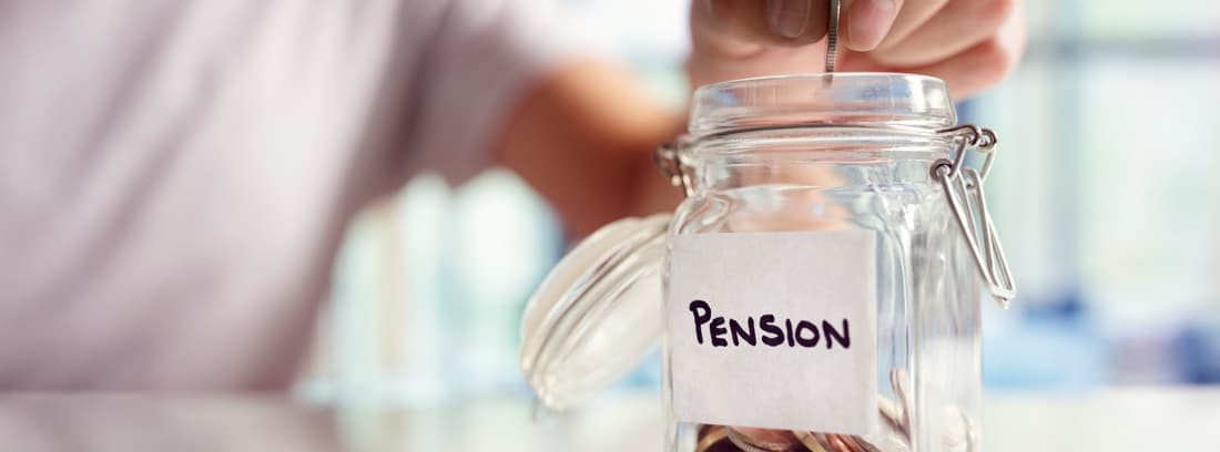 Mano introduciendo monedas en un tarro donde está escrito pensión