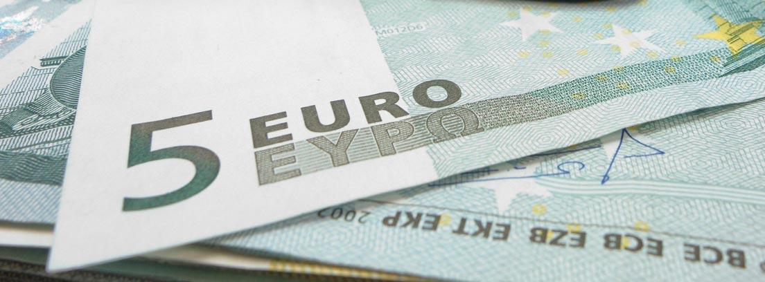 Varios billetes de 5 euros saliendo de una cartera