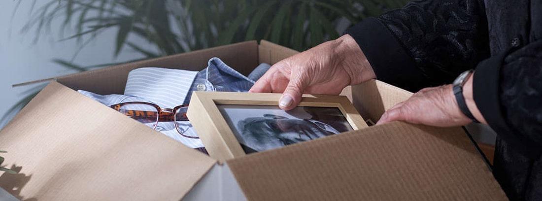 Manos de una anciana guardando una fotografía en una caja de cartón