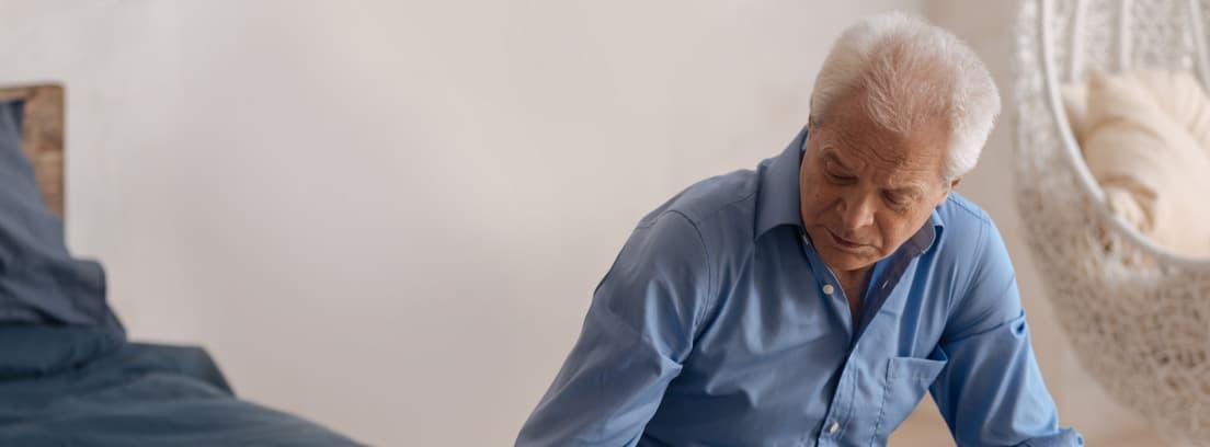 Hombre mayor con bastón sentado en la cama