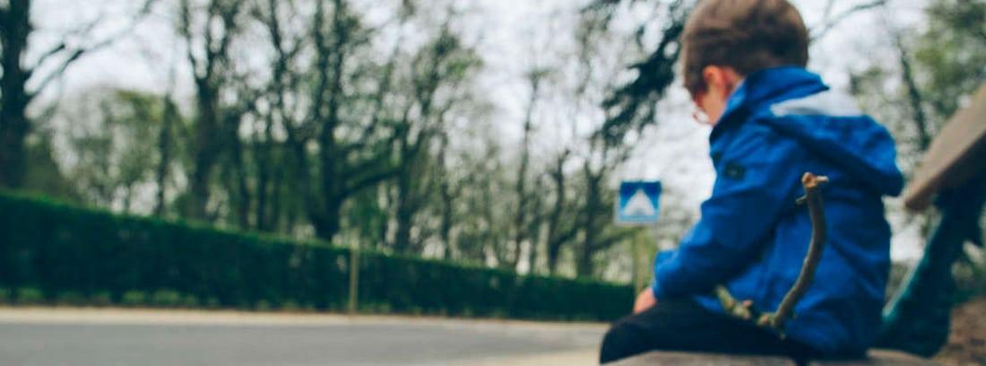 Niño cabizbajo sentado en un banco de la calle