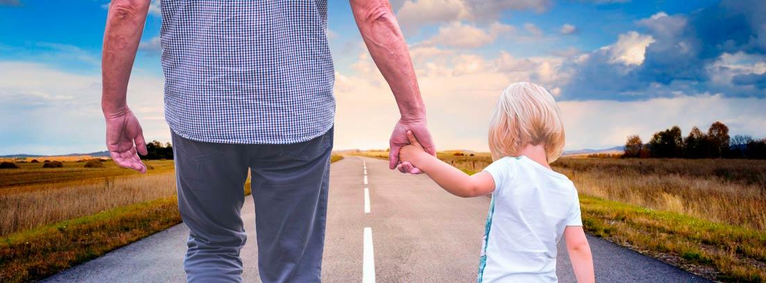 Hombre dando la mano a una niña caminando por una carretera