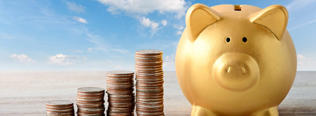 Columnas de monedas junto a una hucha de cerdo