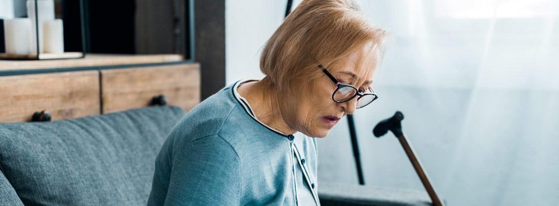 Mujer sentada en un sofá con unos folios y una calculadora
