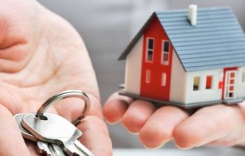 Manos sujetando unas llaves y una casa