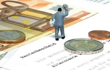 Figura de un hombre sobre papeles, monedas y billetes