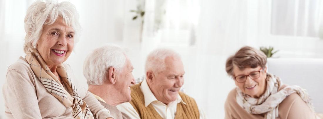 Cuatro personas mayores sentadas en sofá en un ambiente distendido