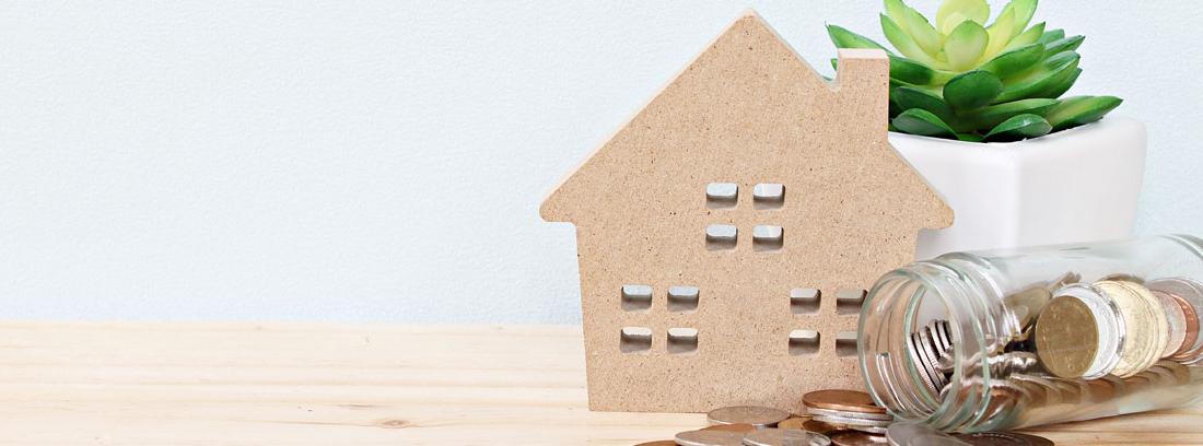casa de miniatura sobre una mesa con un bote de monedas