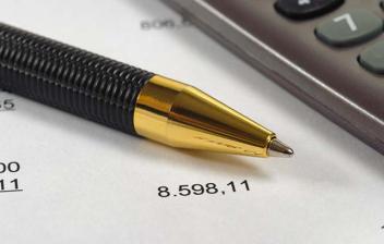 Hoja con cálculos con un bolígrafo y una calculadora