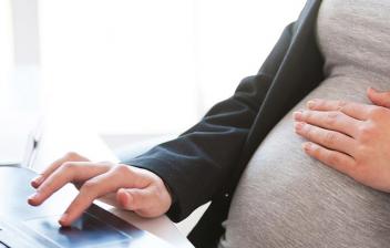 Mujer embarazada trabajando con un portátil
