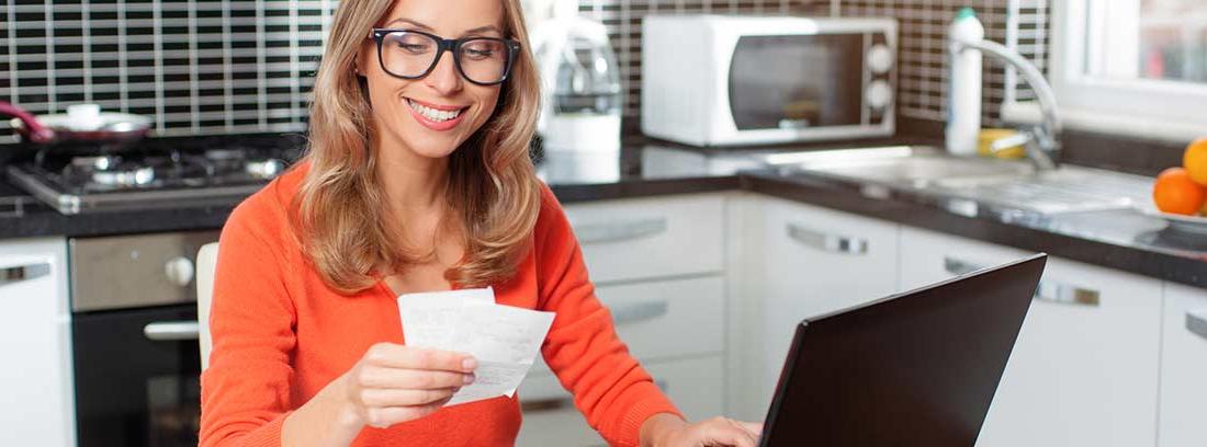 mujer en la mesa de una cocina con portátil y recibos