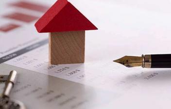 Casa hecha con bloques de juguete, pluma y llave sobre unos papeles