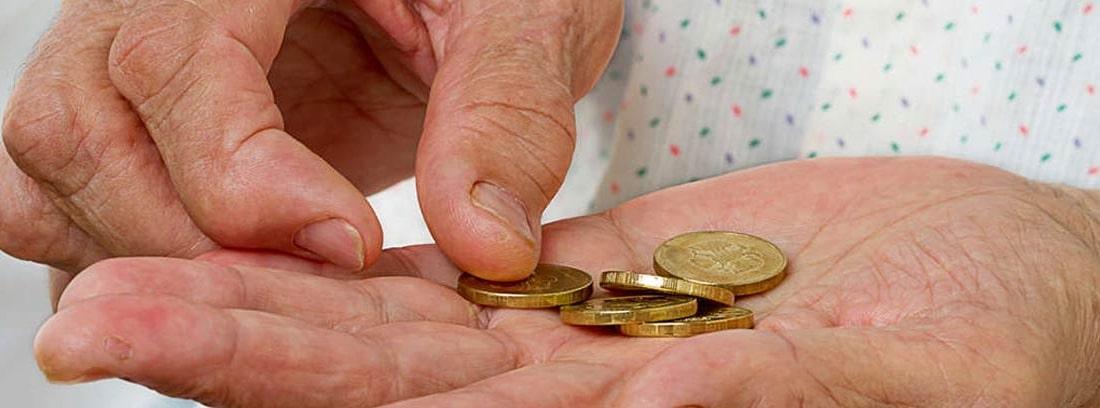 Manos de persona mayor con unas monedas