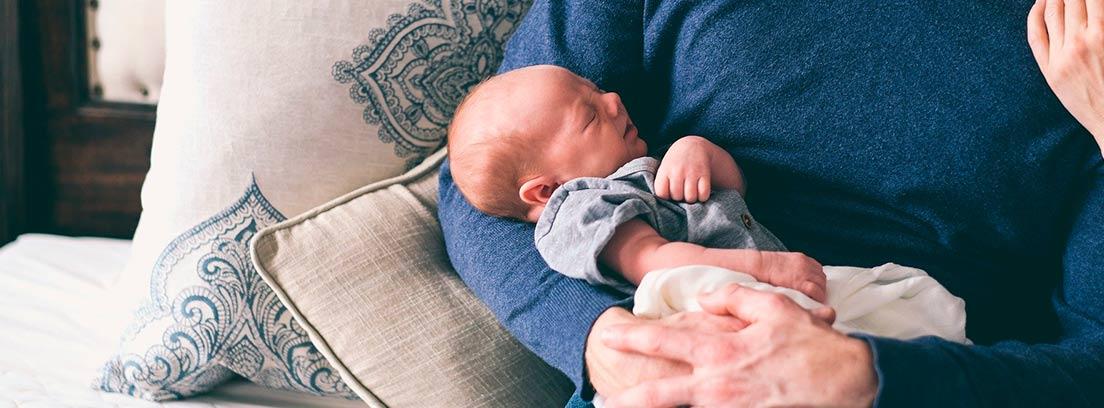Hombre sujetando en brazos a un bebé recién nacido