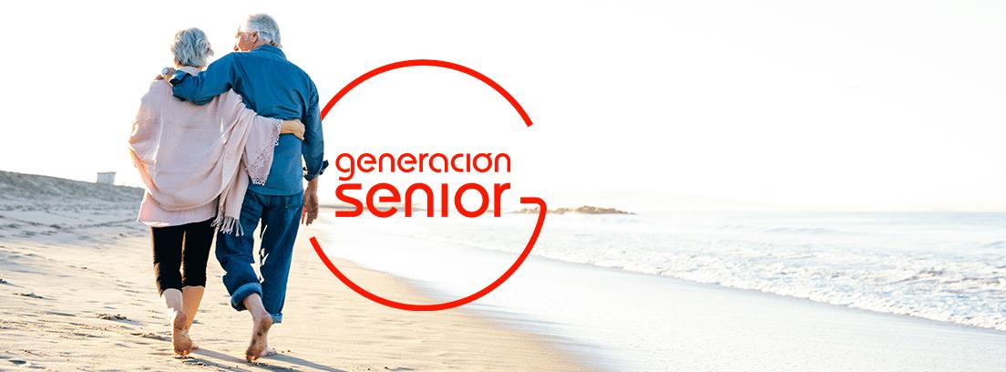 ¿Cuantos viajes con el imserso puedo hacer: pareja de seniors de espaldas paseando por la playa