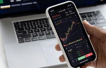 Hombre mira una gráfica de Bolsa en un smartphone