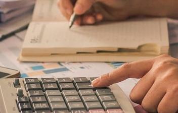 Manos con boli usando una agenda y una calculadora