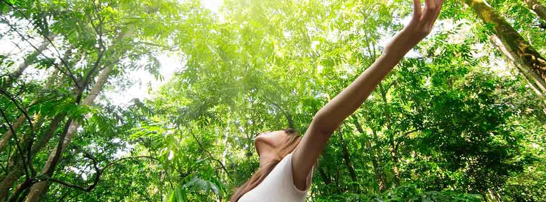 Mujer con los brazos abiertos en un bosque