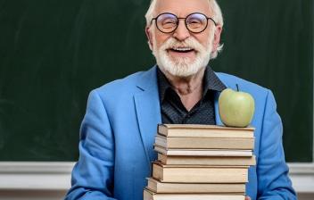 Profesor sujetando una pila de libros